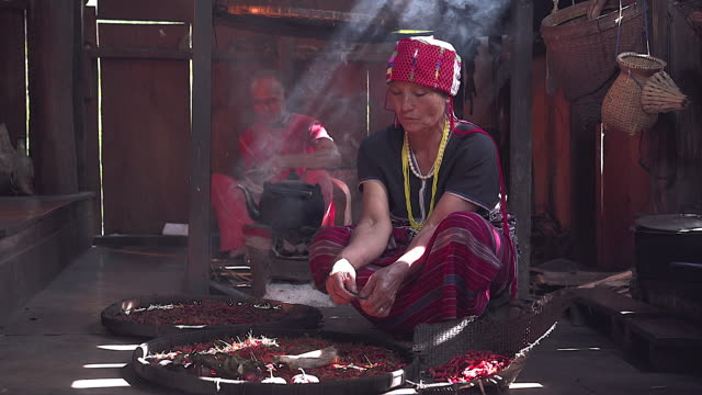 karen elderly woman sitting in separate dried chili to prepare food taken in a karen house the back is a wooden kitchen with no modern technology. - tradition stock videos & royalty-free footage