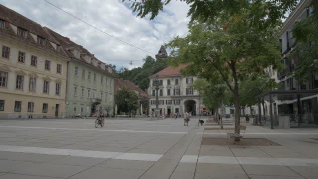 karmeliterplatz overlooked by medieval clock tower in graz old town, graz, styria, austrian alps, austria, europe - städtischer platz stock-videos und b-roll-filmmaterial