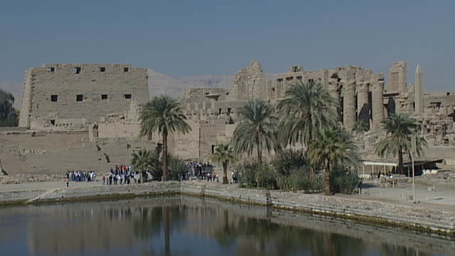 karnak temple complex. view of sacred lake surrounded by palm trees. - spirituality stock videos & royalty-free footage