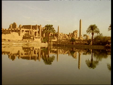 Karnak temple ruins and palm trees reflected in lake