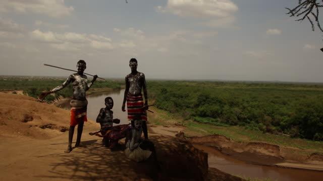 4 Karo tribe boys with white body art near the Omo river Ethiopia