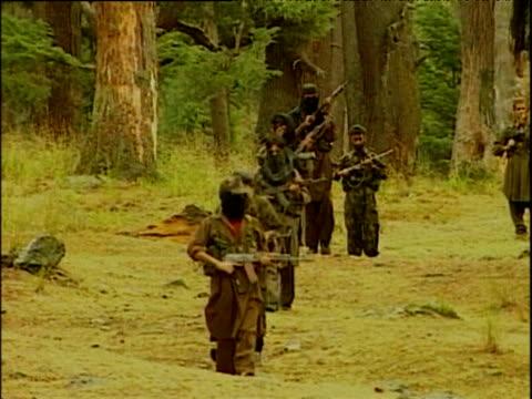 Kashmir militant rebels with hidden identity carry AK 47's patrolling near forest Kashmir; 2001