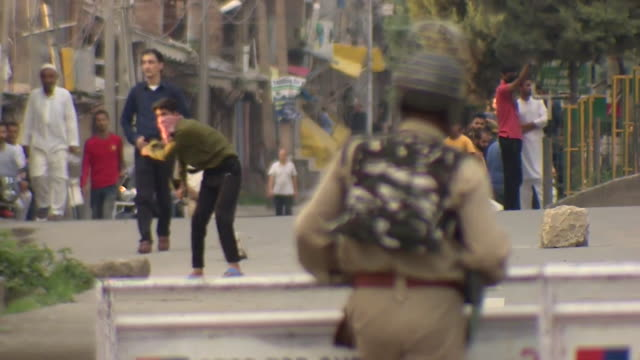 kashmiri throws stones at indian soldier in srinagar as kashmir has speical status removed and place goes into lockdown - india stock videos & royalty-free footage