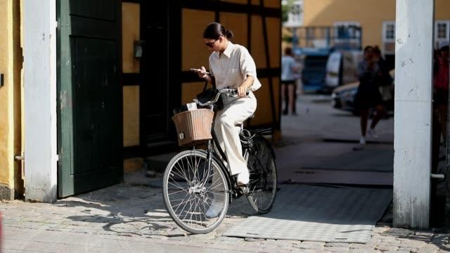 katarina petrovic rides her bike wearing a creme white dress during the copenhagen fashion week spring/summer 2019 on august 9, 2018 in copenhagen,... - vestito bianco video stock e b–roll
