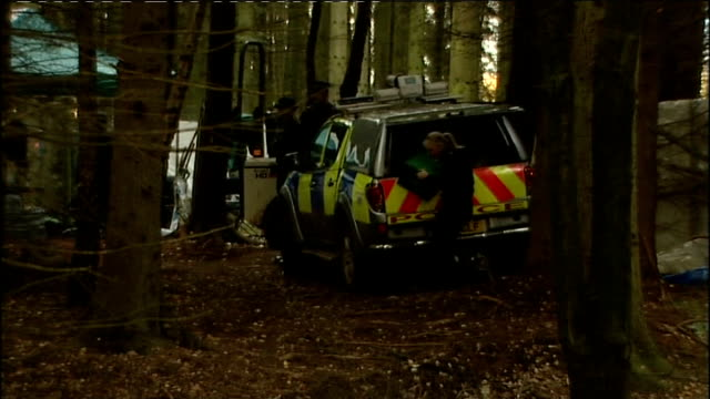 police find body; england: gloucestershire: redmarley: redhill farm: ext various shots of police forensic tarpaulin and police vehicles in woodland... - 防水シート点の映像素材/bロール