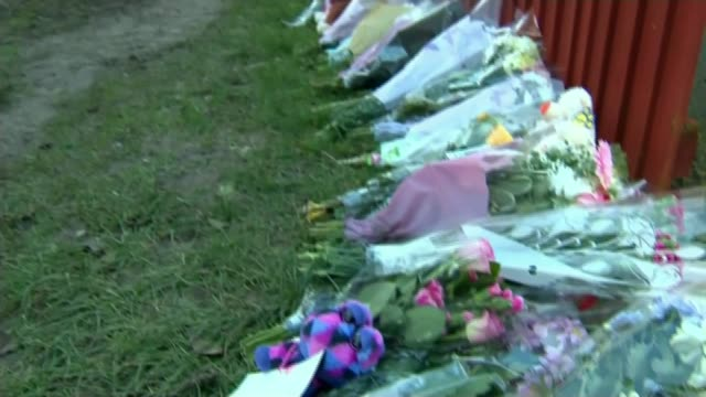 16 year old girl admits to killing EXT Floral tributes for Katie Rough lined against fence Police tape with flowers in background Message on flowers