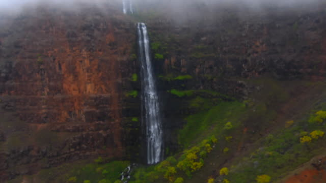 Kauai Hawaii aerial of waterfall from helicopter of the breath-taking Na Pali coast canyons cliffs Na Pali-Kona Forest Reserve 4K