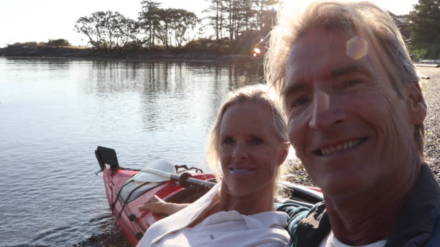 Kayak couple relax on beach after paddle, portrait