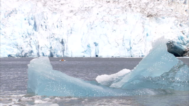 kayak floats in the ocean next to giant ice shelf. - shelf stock videos & royalty-free footage