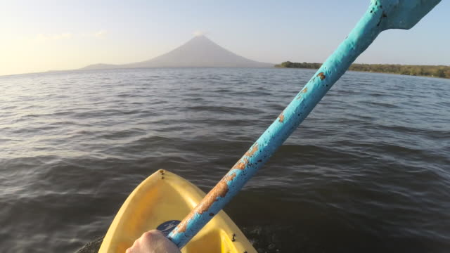 POV kayak on a lake in front of volcano Concepcion. Man kayaker canoeing in a quiet Cocibolca Nicaragua lake at Ometepe island.