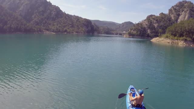 kayak on the lake between mountains - sportschützer stock-videos und b-roll-filmmaterial