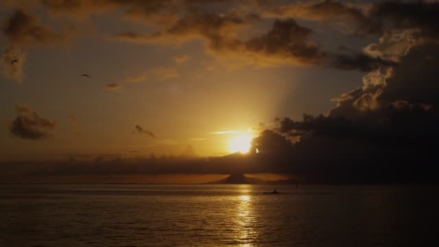vidéos et rushes de kayak paddling in front of an island sunset - île d'huahine
