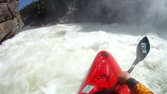 POV of kayaker descending mountain river, by waterfall