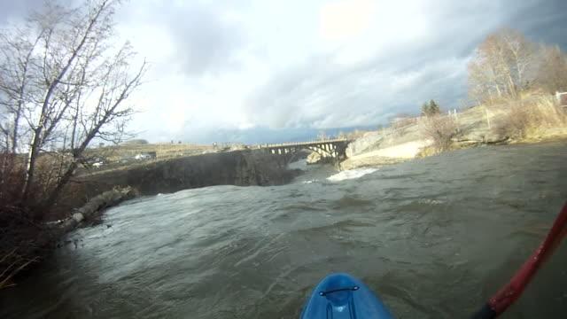 POV of kayaker descending turbulent river, bridge