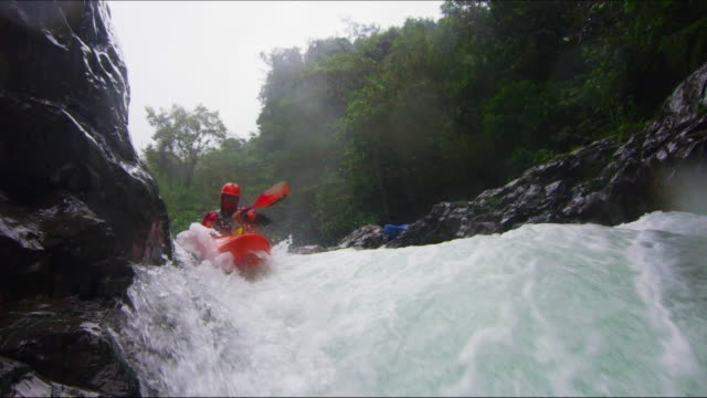 Kayaker drops down water fall in slow motion