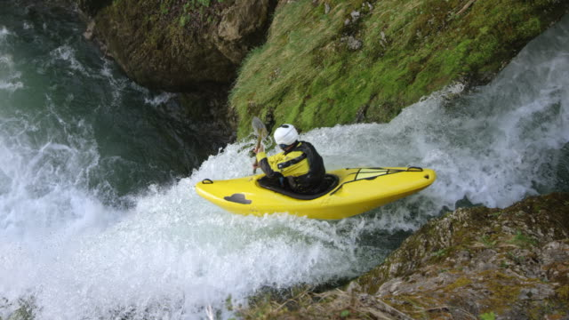 slo mo kayaker in a yellow kayak running a waterfall and diving into the plunge pool - kayak video stock e b–roll