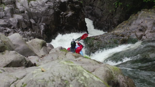 Kayaker navigates through river rapids