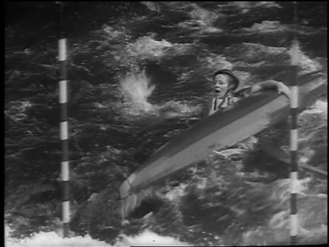 vídeos y material grabado en eventos de stock de kayaker on river rapids capsizing in slalom competition / czechoslovakia / news. - sólo hombres jóvenes