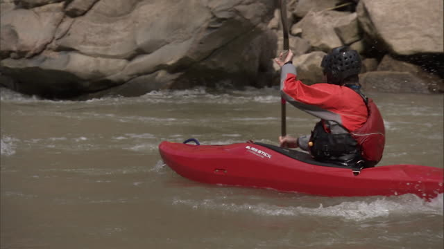 a kayaker paddles along a river. - sports helmet stock videos & royalty-free footage