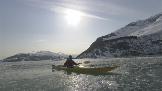 a kayaker paddles along icy prince william sound, alaska. - prince william stock videos & royalty-free footage