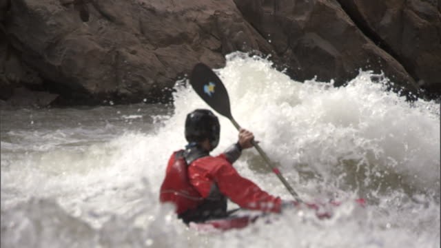 a kayaker paddles through furious rapids in the grand canyon. - sports helmet stock videos & royalty-free footage