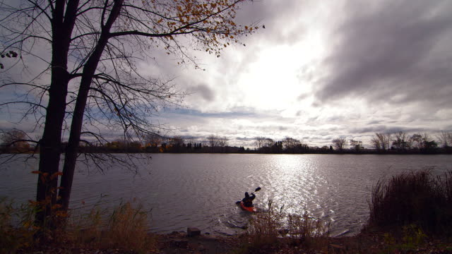 WS of kayaker paddling away on the St. Lawrence River