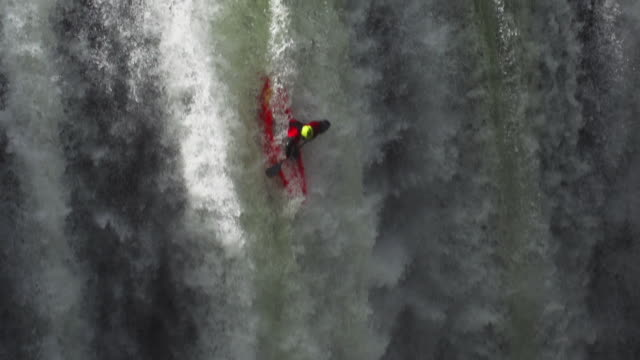 Kayaker riding down waterfall