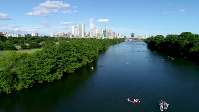 kayakers along the colorado river with the austin texas skyline - nature stock videos & royalty-free footage