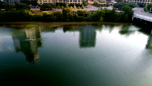 vídeos de stock e filmes b-roll de kayakers on town lake early morning reflection pan up to austin skyline - town