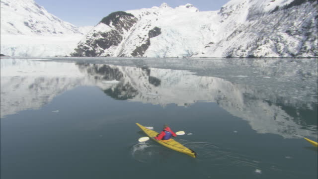 kayakers paddle across the icy, calm waters of prince william sound. - prince william stock videos & royalty-free footage