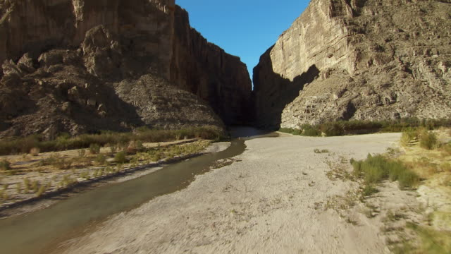 kayakers paddle downstream at the mouth of the santa elena canyon in big bend national park, texas. - 低い点の映像素材/bロール