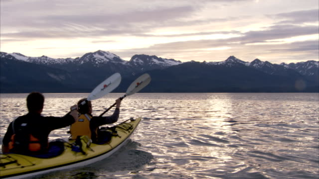 kayakers paddle toward alaska's mountainous coast. - pagaiare video stock e b–roll