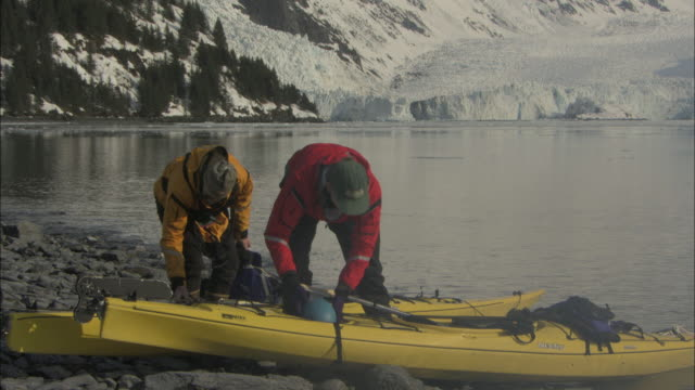 kayakers sort through gear before launch. - 準備点の映像素材/bロール