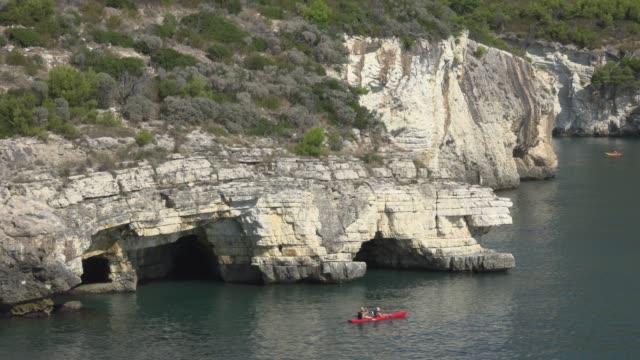 vídeos y material grabado en eventos de stock de kayaking at grotta sfondata grande at rocky coast with white limestone rocks - península