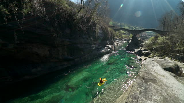 kayaking down clear water river under stone arch bridge - ticino canton stock videos and b-roll footage