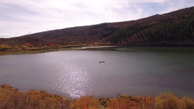 stockvideo's en b-roll-footage met kayaking far side tracking, mountain reveal fall colors lake reflection, wildlife, foliage short aerial, 4k, 4s, 62of96, stock video sale - drone discoveries llc 4k sports - sale