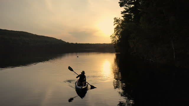 kayaking on remote lake at sunset in silhouette. - seeufer stock-videos und b-roll-filmmaterial