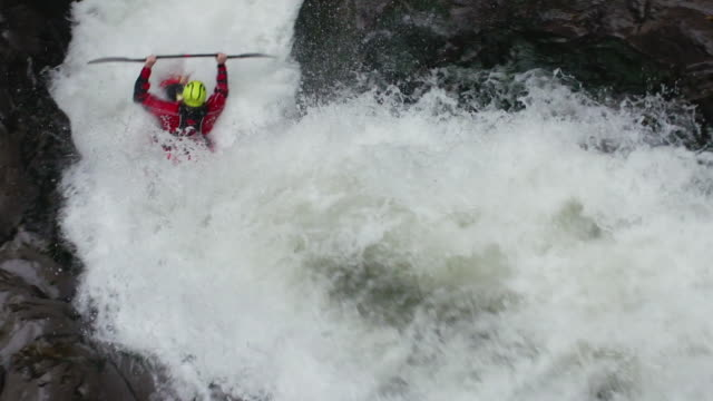 Kayaking through rapids passing directly under camera