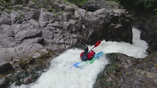 kayaking through rocky river rapids - kajakdisziplin stock-videos und b-roll-filmmaterial