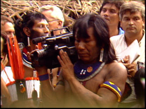 A Kayapo Indian reporter holds a news camera at a press conference given by Sting in the Amazon about saving the rainforest