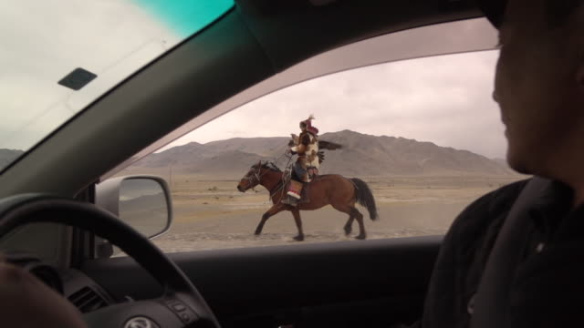 kazakh eagle hunter in mongolia on horse with golden eagle alongside car - independent mongolia stock videos & royalty-free footage