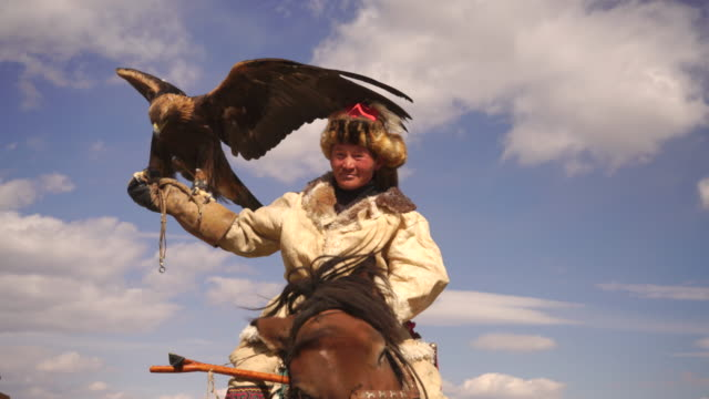 kazakh eagle hunter in mongolia on horse with golden eagle - independent mongolia stock videos & royalty-free footage