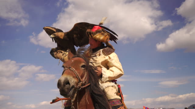 kazakh eagle hunter in mongolia on horse with golden eagle - hunter stock videos & royalty-free footage