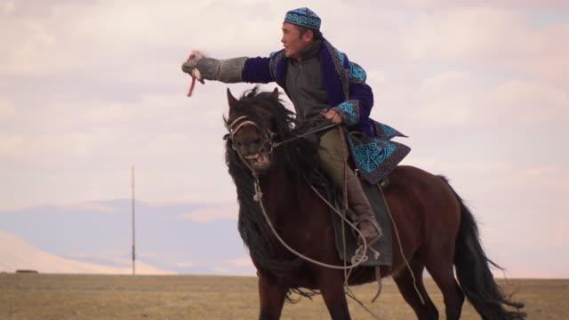 kazakh eagle hunters in mongolia compete at golden eagle festival - kazakhstan stock videos & royalty-free footage