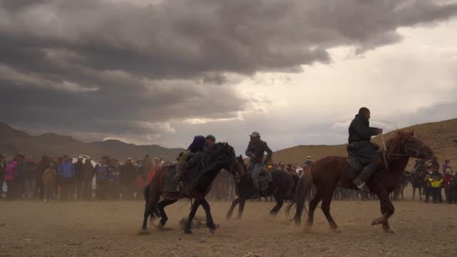 vídeos de stock, filmes e b-roll de kazakh eagle hunters in mongolia play kokbar game at golden eagle festival - montar um animal