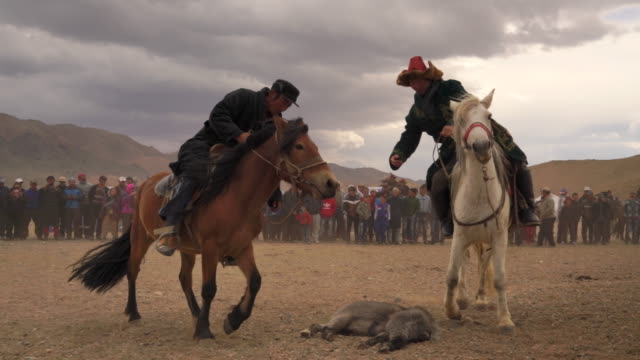kazakh eagle hunters in mongolia play kokbar game at golden eagle festival - mongolei stock-videos und b-roll-filmmaterial