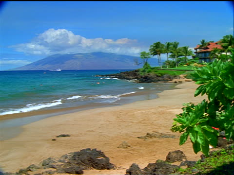 Kealani Beach with building + West Maui Mountains in background / Maui, Hawaii