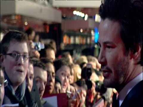 vídeos de stock e filmes b-roll de keanu reeves signs autographs for crowds of fans on bafta red carpet london 12 feb 05 - autografar