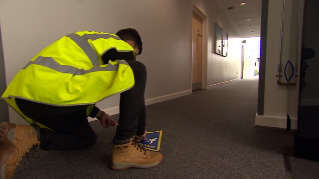 keep moving' coronavirus social distancing sign being applied to the floor of a school corridor - stato di emergenza video stock e b–roll