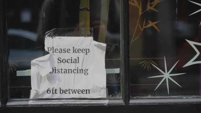 keep social distancing sign on a window display of a closed cafe in manhattan downtown 4k uhd video footage - unemployment covid stock videos & royalty-free footage